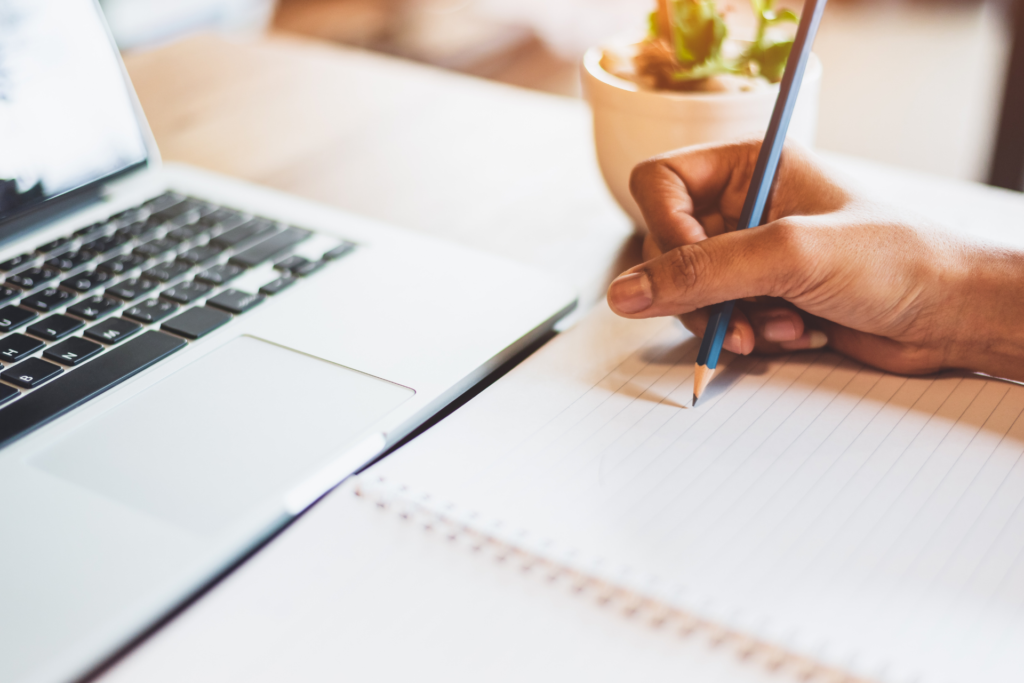 A woman is holding a pen in her hand and starts to write something in a notebook. In front of her is a laptop.