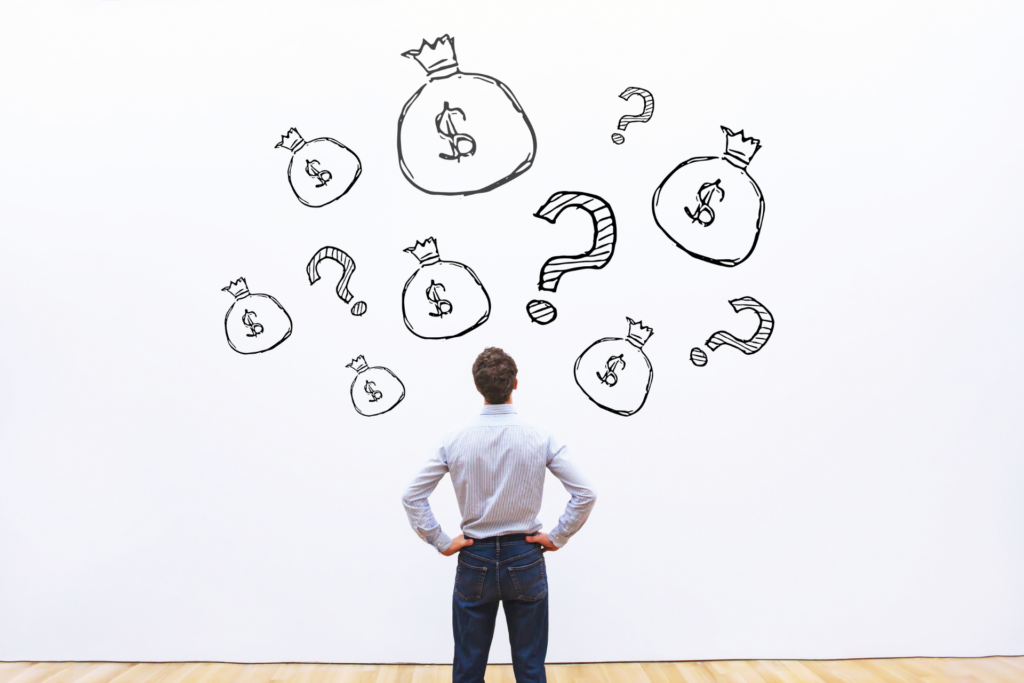 A man is standing in front of a wall. On the wall some questionmarks and money bags are drawn.