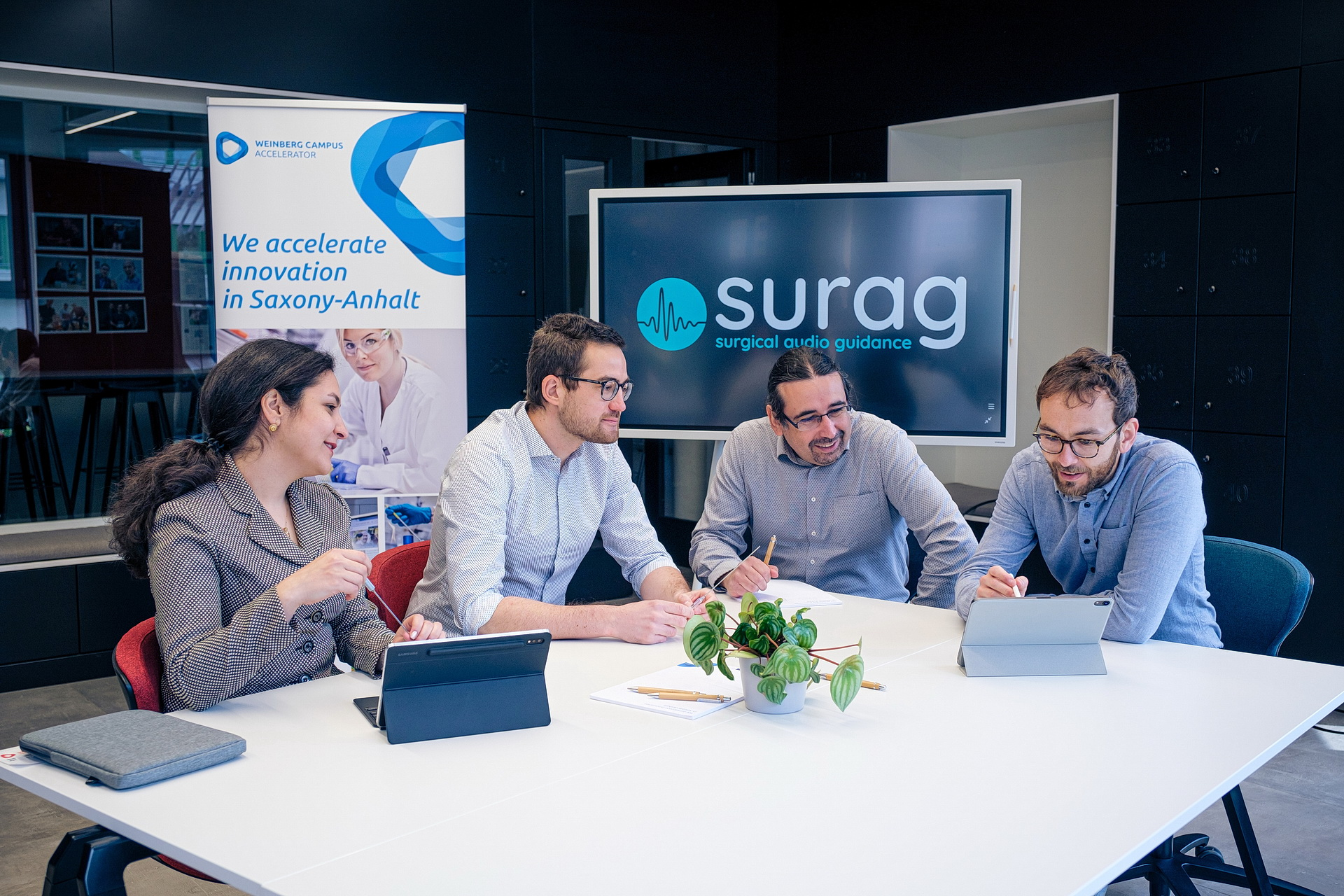 Four people sitting together on a table discussing a topic.