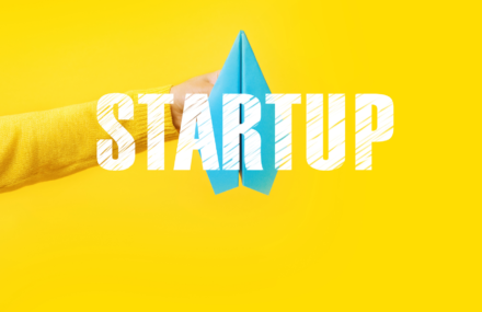 """You can see the hand of a person in front of a yellow wall holing a paper rocket. The word """"Startup"""" is written in front of that."""