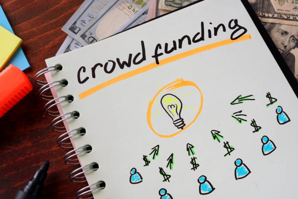 """A book is placed on a desk next to some pens, sticky notes and money. On the paper you can read """"crowdfunding"""" and underneath people with dollar signs are outlined. From there arrows point to a lightbulb."""
