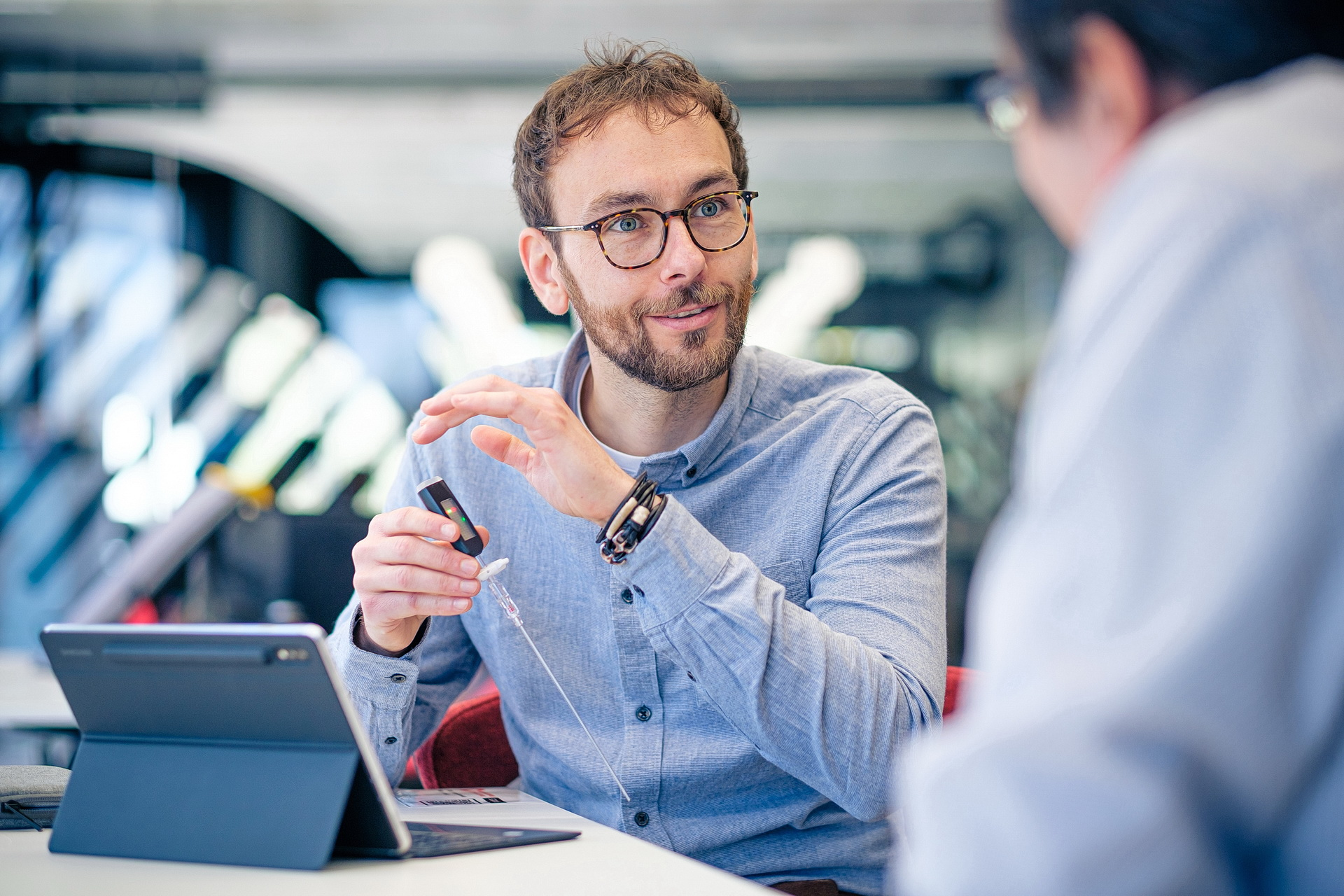 A man talks to another man while holding a prototype in his hands.