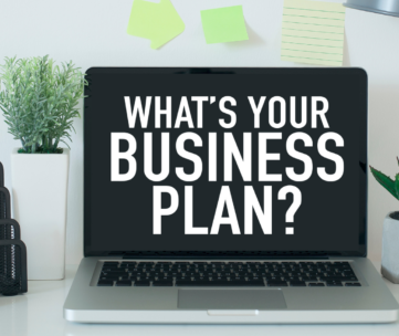 """A computer is on a desk next to plants, a lamp and some pens. On the screen it is written """"What's your next Business Plan?"""""""